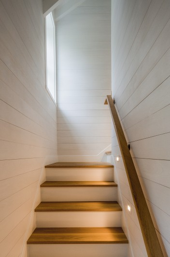 A stairwell is lit with step lights to guide residents up safely, with white wood-clad walls and a window ushering in light from outside